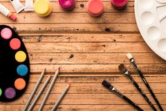 Ready to paint. Artistic materials: watercolors and brushes on a wooden table. Copyspase. Top view. Frame royalty free stock image