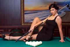 Ready to play billiards. Beautiful girl sitting on the billiards table Stock Image