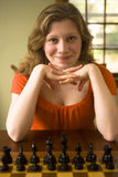 Ready to play chess. Teen woman has look of superiority as she readys for her opening move in a game of chess stock photo