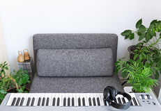 Ready to play. Electric piano and comfortable armchair for a musician Stock Image
