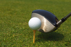 Ready to play golf. Golf ball with tee on grass with a driver Stock Photo