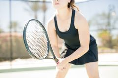 Ready to play tennis. Close up of racket in hands of female tennis player reading to face the serve on outdoors court during training Stock Photography
