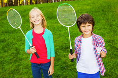We are ready to play!. Two cute little children holding badminton rackets and smiling while standing on green grass together royalty free stock photography