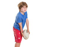 Ready to play. Young boy posing with rugby league ball pretending to throw it, with lots of copy space Stock Photography