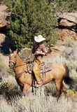 Ready to Ride. Hard working cowgirl riding her horse in the desert stock photos