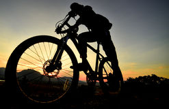 Ready to ride a bike. Biking and nature passion.Bike riding silhouette.Sunrise and sport position Royalty Free Stock Photography