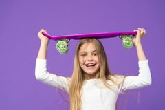 Ready to ride. Skateboarding is fun. Happy skater girl on violet background. Childhood development and happiness. Hipster girl. Little child smile with penny stock photos