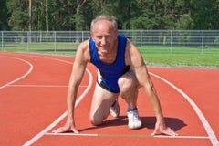 Ready to run. Senior runner in starting position on track Stock Photos