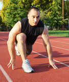 Ready To Run. Male athlete getting ready to run on an athletic track with trees in the background on a sunny day Stock Photo