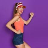 Ready To Run. Happy girl in orange shirt and sun visor posing on the run. Three quarter length studio shot on violet background Royalty Free Stock Photo