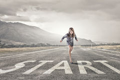 She is ready to run this race. Young determined businesswoman on road standing in start position Royalty Free Stock Photo