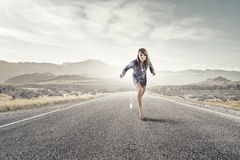 She is ready to run this race. Young determined businesswoman on road standing in start position Stock Photo