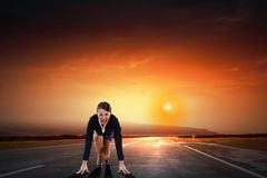 Ready to run. Young determined businesswoman standing in start position Royalty Free Stock Photo