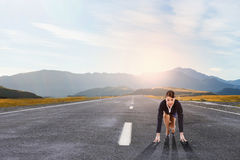 Ready to run. Young determined businesswoman standing in start position Stock Images