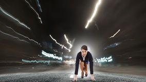Ready to run. Young determined businesswoman standing in start position Royalty Free Stock Image