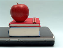 Ready to school. Laptop with books, pencils and red apple on blue background Stock Images