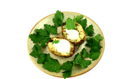 Ready to serve. Halved baked potato on a plate surrounded by parsley's leaves on white Royalty Free Stock Images