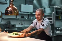 Ready to serve. Young smiling chef with tattoos on his arms, in black apron holding ready dish in modern restaurant. Kitchen. Food concept royalty free stock photography