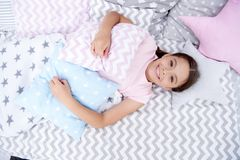 Ready to sleep. Girl smiling happy child lay on bed with star shaped pillows and cute plaid in her bedroom. Bedclothes. For children. Modern fashionable royalty free stock photography