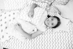 Ready to sleep. Girl smiling happy child lay on bed with star shaped pillows and cute plaid in her bedroom. Bedclothes. For children. Modern fashionable royalty free stock photos