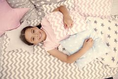 Ready to sleep. Girl smiling happy child lay on bed with star shaped pillows and cute plaid in her bedroom. Bedclothes. For children. Modern fashionable stock image