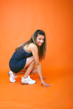 Ready To Sprint. Profile of smiling brunette teenage girl crouched with her hands braced on the ground, ready to sprint.  Vertical shot Stock Photos