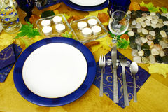 Ready to start a dinner. Plate put on the table covered with autumn leaves Royalty Free Stock Photo