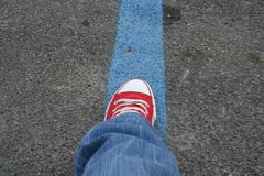 Ready to start traveling. Foot in red and white shoes stands on blue line on road. Blue jeans wearing Royalty Free Stock Photography