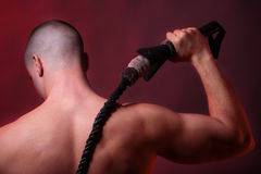Ready to strike. Close-up of a muscular male preparing to strike with his whip. Rear view Stock Image