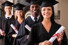 Ready to success. Four college graduates standing in a row and smiling Royalty Free Stock Image
