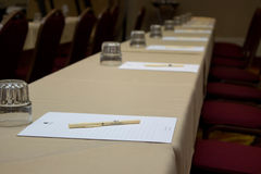Ready To Take Notes. A picture of a long empty table with one piece of paper   and a pen, positioned neatly in front of each seat Stock Photography