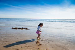Baby Girl walks along a beautiful beach Stock Photo