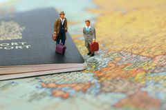 Ready to travel. Mini people standing on canadian passport and world map ready to travel Stock Images