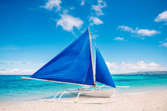 Ready to travel by blue sail boat. Tropical turquois sea on the background. Royalty Free Stock Image