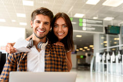 We are ready to travel. Joyful loving couple is waiting at airport and smiling. Man is sitting and using laptop. Woman is hugging him and holding tickets Stock Photography