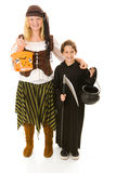 Ready to Trick or Treat. Adorable little boy in halloween costume getting ready to trick or treat with his sister.  Full body isolated on white Royalty Free Stock Photo