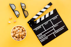 Ready to watch film. Clapperboard, glasses and popcorn on yellow background top view Royalty Free Stock Photography
