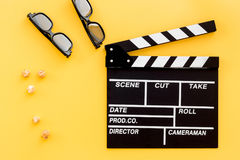 Ready to watch film. Clapperboard, glasses and popcorn on yellow background top view Stock Image