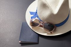 Ready for travel concept. Passport, hat and sunglasses on a black background royalty free stock photography