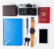 Ready for travel isolated objects. Phone, watches, keys, notebook, passport, photo camera, purse on white background. royalty free stock photography