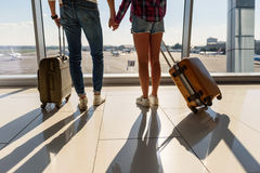 We are ready for trip. Close up of male and female legs standing in airport near window. Loving couple is holding hands and carrying luggage Royalty Free Stock Photos