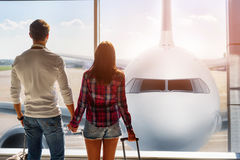 We are ready for trip. Forward to future. Young loving couple is watching plane though window before departure. They are standing at airport and holding hands Stock Image
