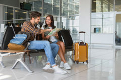 We are ready for trip. Happy young couple is sitting in airport near suitcase. They are reading map and smiling Royalty Free Stock Photography