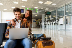 We are ready for vacation. Excited young loving couple is waiting for flight at airport. Man is sitting and using laptop. Woman is embracing him and smiling Royalty Free Stock Photo