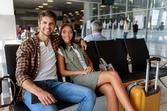 We are ready for vacation. Happy young loving couple is sitting at airport and waiting for flight. They are embracing and smiling Stock Photography