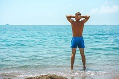 Young and man in swimming trunks standing on the beach and looking at the sea stock images