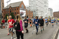 Ready Willing and Able - Liverpool Marathon 2017. A disabled runner makes his way along the course with help from friends Royalty Free Stock Photography