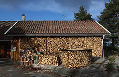 Ready for winter. A wood shelter stacked with firewood for the winter season Stock Image