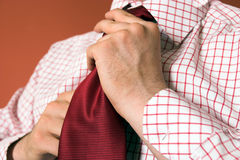 Ready for work. Man tying a red necktie Royalty Free Stock Images