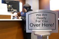 We are ready for you over here sign with blur motion people at service counter. Inside TD bank Stock Photos